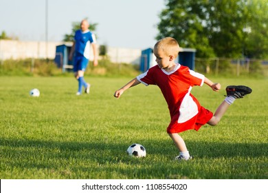 The 4 years old boy is shooting the soccer ball on soccer sport training outdoors on playing field.