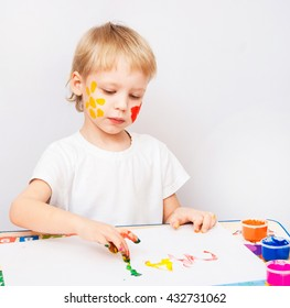 4 years old child painted letters with hands. Exciting baby boy playing with paint isolated on white background. Boy wearing white t-shirt. Kid sitting at table learning to write letters.