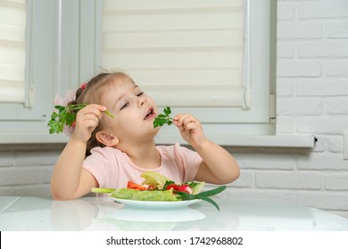 4 years old girl sitting in the kitchen at the table and eating vegetables, in the hands of a sprig of parsley. preschool nutrition rules