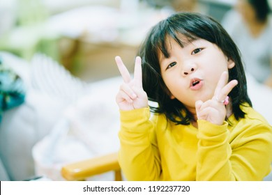 4 years old little asian girl doing the exercise of math at home and show two fingers.