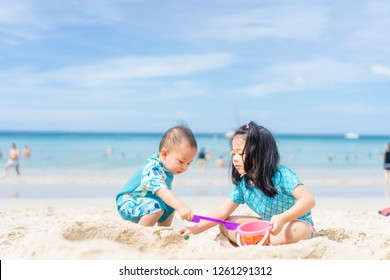 4 years old Little asian girl playing on the beach with her 1 year old baby brother.Family with children at the beach. Love, trust and tenderness.Sibling on Vacation summer and relax concept.