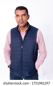 40 year old man looking at camera with hands in pocket, wearing a pink long sleeve shirt and a cold blue vest in a studio with white background