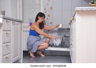 40 year old woman putting dishes in the dishwasher. Woman doing housework, puts dishes in the washing machine