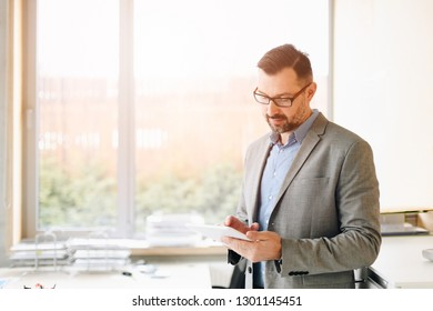 40 years old handsome businessman working on tablet computer in office. Man working in office