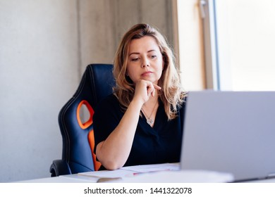 40 years old woman working on laptop computer in the office