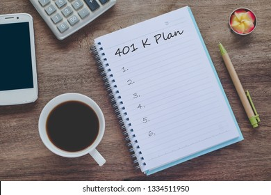 401K Plan text on book note with cup of coffee, pen and smartphone.