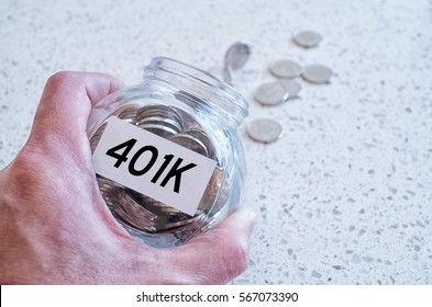 401k retiring plan concept with hand holding a glass jar full of coins on a marble counter top