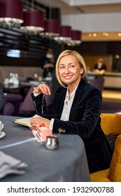 40-45 years old woman after business meeting in restaurant, smile, enjoy free time, looking at side, wearing elegant wear