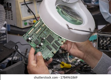 A 40-45-year-old man in a medical mask looks through a magnifying lens at an electrical Board from a computer, close-up. Repair of office equipment and equipment at home.