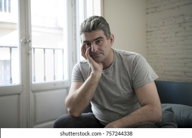 40s or 50s sad and worried man with grey hair sitting at home couch looking depressed and wasted in sadness face expression in depression and life problems concept