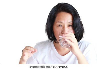 40s Asian or Japanese women in white casual tee with out make up drinking water after swallow a medicine.People have increasingly treated depression with medication.Concept of people popping pills.