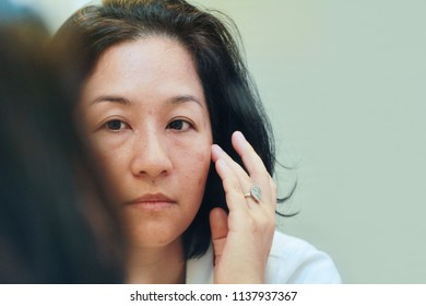 40s Asian woman looking on her face skin in the mirror and look worried or concern about the Aging skin problem.Brownish colored patches or melasma appear on the cheeks.It typically occurs on the face