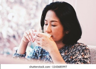 40s beautiful Asian woman sipping or taste her hot tea from the white cup.Sweet relax moment of modern housewife happy with tea in the afternoon.Looks calm and peaceful.Concept of Japanese housewife.