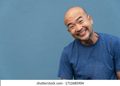 40s of smiling funny Japanese portrait man in t-shirt on blue cement background