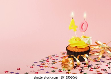 40th birthday cupcake with candles, sprinkles and ribbon on pink background. Card mockup, copy space. Birthday, party, holiday concept