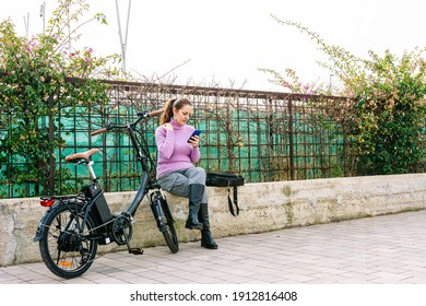40-year-old woman, talking on the phone next to her electric bike while having a coffee to go.
