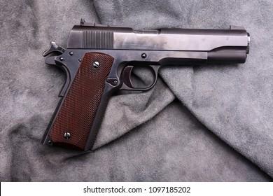 .45 caliber 1911 semi automatic pistol.  Vintage 1911 .45 caliber pistol on blue grey leather background.