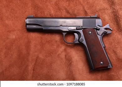 .45 caliber 1911 semi automatic pistol. 1911 .45 caliber army pistol on brown leather background.