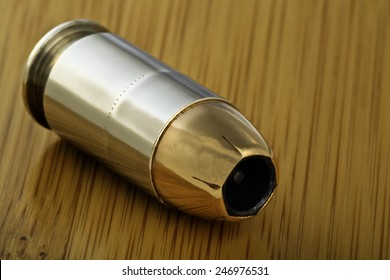 45 caliber jacketed hollow point bullet cartridge live round for semi-automatic handgun gun, bamboo wood background