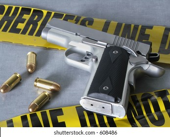 A .45 caliber pistol with bullets, with crime scene tape.