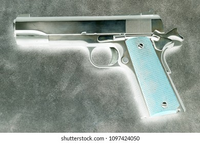 .45 caliber semi automatic pistol on a leather background. Inverted image for an artistic effect.