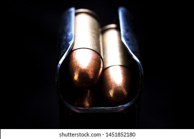 .45 caliber submachine gun cartridges in box magazine on black background