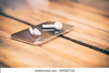 A 45 degree view of a set of wireless earbud headphones and mobile phone lying on a rustic wooden table.
