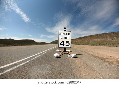 a 45 mile per hour speed limit sign on a highway in the desert. shot with a fisheye lens for a fun distorted image