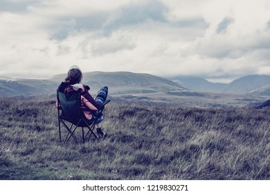 45 years old male with long hair dressed in hipster style outdoor wear, sitting on camping chair enjoying tranquility and beautiful view on scenic mountain valley in Uk.Human and nature, solitude.