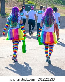 4-6-2019 Tulsa - Two women participating in the Tulsa Color Run walk away from camera with long rainbow colored hair, rainbow striped tutus and socks and long gloves - other runners in distance