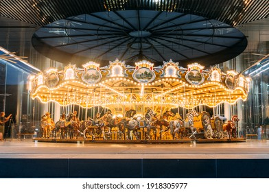48-horse Merry-Go-Round wooden carousel ride at fair Lit up at night.