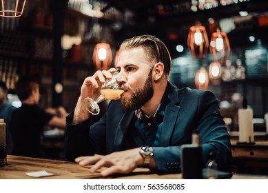 49/5000 bearded man in a suit with a telephone drinks something