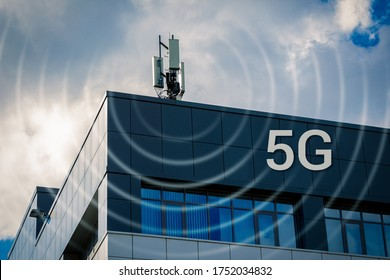 4G, 5G transmitters in an urban environment. Cellular base station with transmitting antennas on the roof of an office building against a cloudy sky.