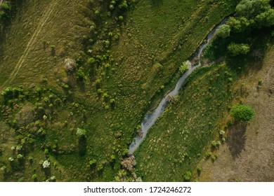 4K aerial drone shoot. Flying over a beautiful green forest in a rural landscape. Top view of trees in forest background. Drone photography. Forest river, rural road.