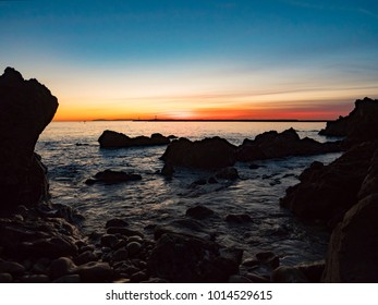 4k Beach Sunsets with Rocks and Tide Pools Under Blue Skies with Orange Horizon in Paradise