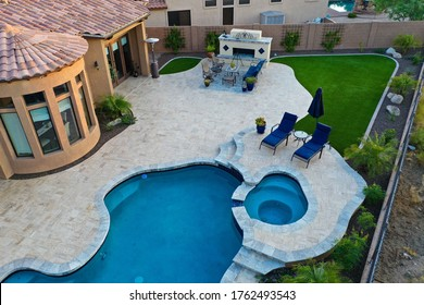 A 4k high resolution aerial view of a pool and spa with a travertine patio and outdoor fireplace.
