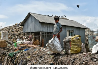 4th August 2018, Guwahati, Assam, India. Kid rag picker sorting recyclable materials in a large dumping ground in Guwahati, Assam, India.
