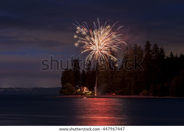 4th of July Fireworks Display. Independence Day signals fireworks and beach BBQ. Here the celebrations take place at Agate Pass between Bainbridge Island and the Olympic Peninsula, Washington state.