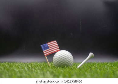 4th July golf ball and flag of America on green grass.