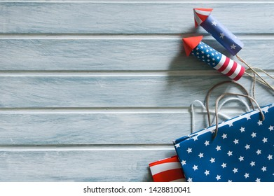 4th July holiday shopping concept. Shopping bags in national american colors and firework rockets over wooden background