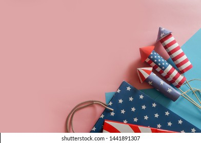 4th July holiday shopping concept. Shopping bags in national american colors and firework rockets over pink background