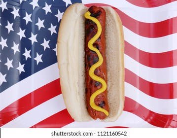 4th of July. A hot dog in a bun with yellow mustard on an American flag paper plate. isolated on white. 4th of July Picnic. Hot dog with mustard.