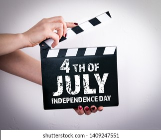 4th of July Independence day of the US. Female hands holding movie clapper