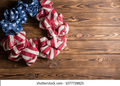 4th July Independence Day wreath in the colors of the USA National Flag with stars and stripes on wood with copy space