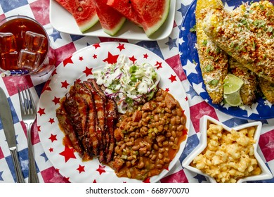 4th of July picnic filled with barbecue brisket, baked beans, coleslaw, corn, mac and cheese, watermelon and iced tea shot from above