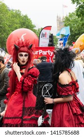 4th June 2019. London, UK. Anti Trump rally in Westminster. A woman in devil costume holds Extinction Rebellion placard at Trump protest.