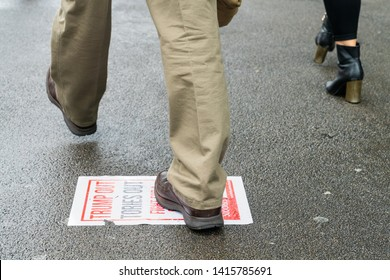 4th June 2019. London, UK. Anti Trump rally in Westminster. A man steps on the paper that says Trump Out Tories Out.