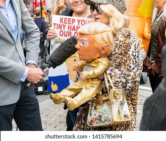 4th June 2019. London, UK. Anti Trump rally in Westminster. A reporter takes an interview from a blonde woman carrying baby Trump and a bag of cash.