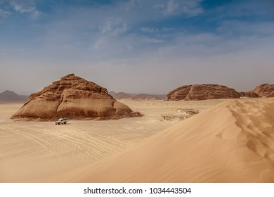 4WD car in desert with dune in foreground