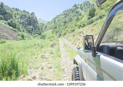 4WD car running on gravel road with nature mountain landscape in Kazakhstan. Adventure and extreme sport